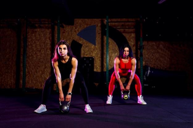 Atleta de duas mulheres atraentes em forma realizando um balanço de kettle-bell no ginásio.