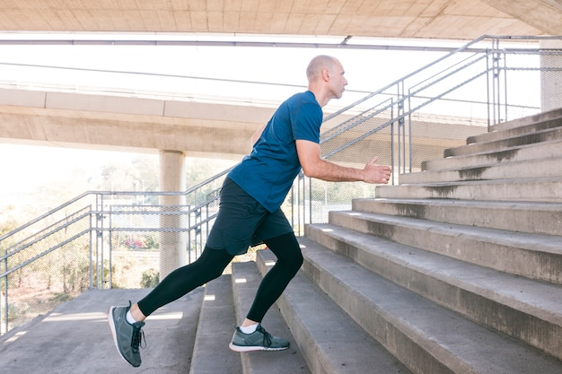 Atleta de fitness masculino correndo na escada de concreto