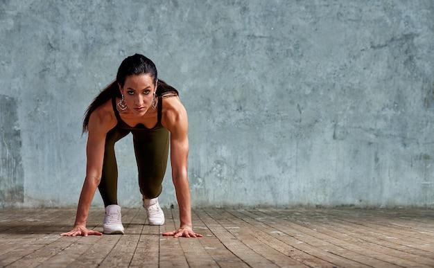 Atleta de fitness no início contra a parede, preparando-se para o sprint
