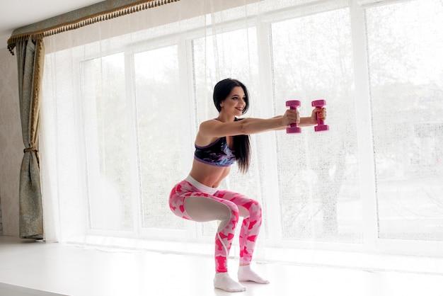 Atleta de fitness sensual realiza exercícios nas nádegas no estúdio. musculação.