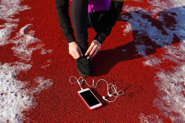 Atleta de garota de tênis preto, agachado na pista vermelha para correr.