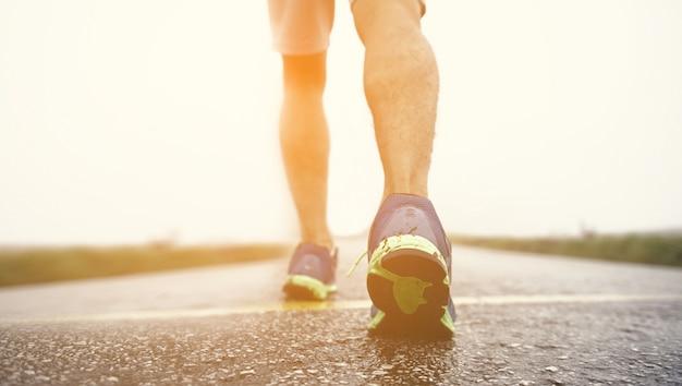 Atleta de homem correndo na estrada. fitness e estilo de vida saudável