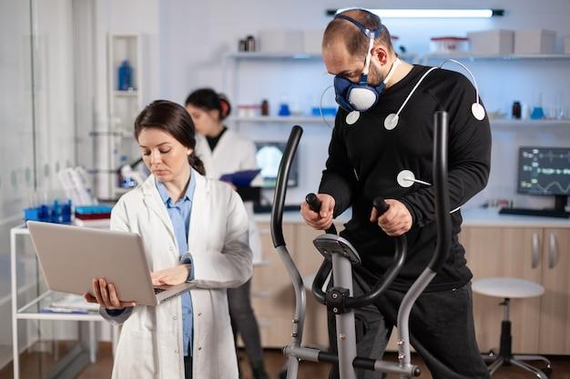 Atleta de homem correndo no cross trainer com eletrodos fixados em seu corpo e máscara. médico usando laptop e controla dados de ekg exibidos em monitores de laboratório, discutindo com o paciente.