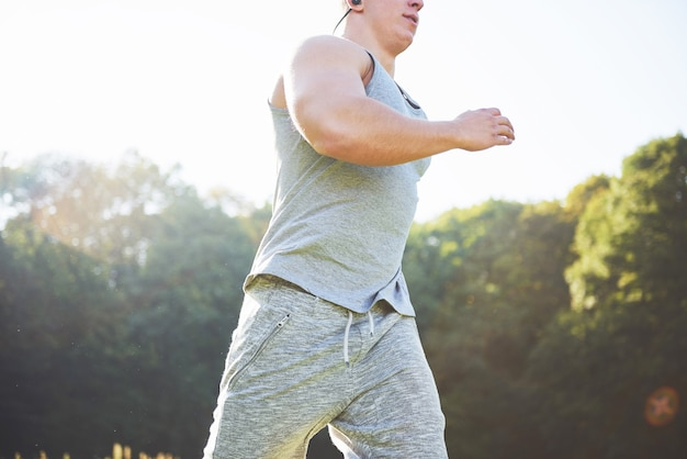 Atleta de homem fitness correndo na natureza durante o pôr do sol.