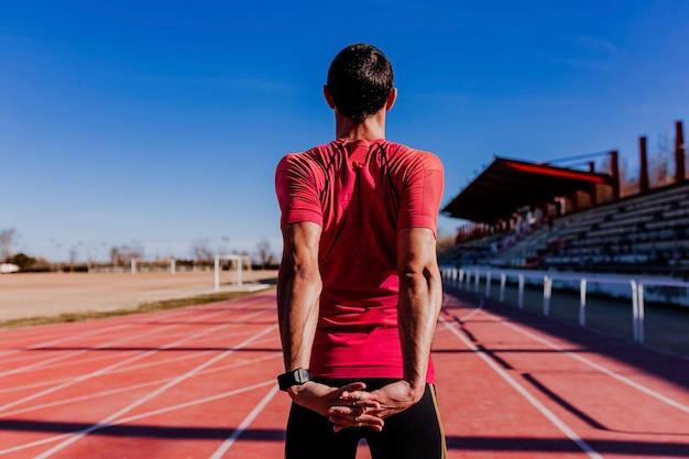 Atleta de homem jovem corredor, estendendo-se na pista de corrida. esportes ao ar livre