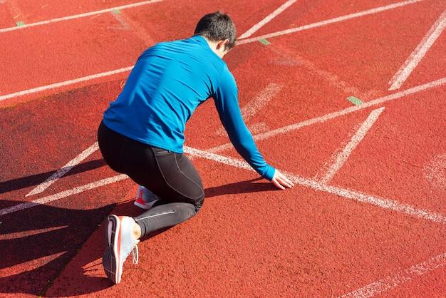 Atleta de homem na linha de partida de uma pista de corrida no estádio.