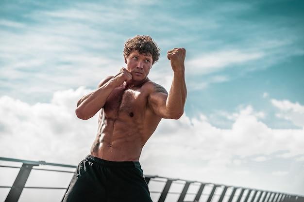 Atleta de jovem musculoso em pé e praticando boxe de sombra ao ar livre de manhã cedo no pi ...