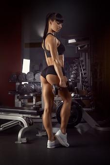 Atleta de jovem musculoso em pé olhando para baixo com as mãos com haltere mulher fisiculturista rel ...