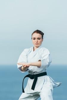 Atleta de karatê feminino jovem batendo um chute alto na grama. ela está usando um cinto preto e quimono branco