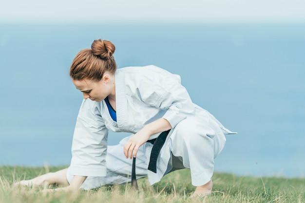 Atleta de karatê jovem ruiva esticando as pernas na grama