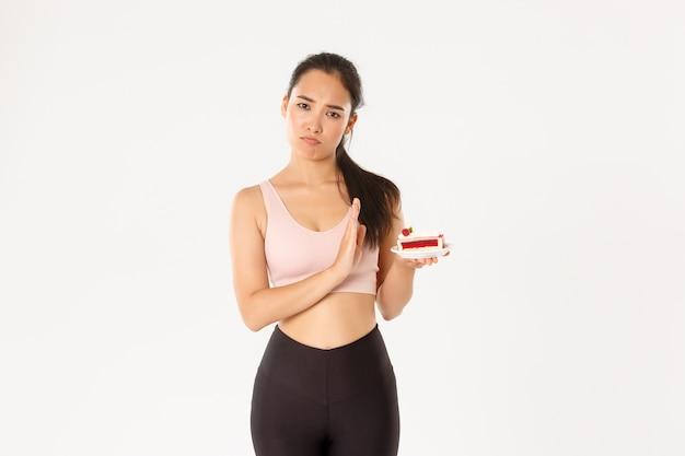 Atleta de menina asiática determinada rejeitando doces, parar de comer junk food durante a dieta, perder peso, recusar comer bolo, fundo branco relutante em pé.