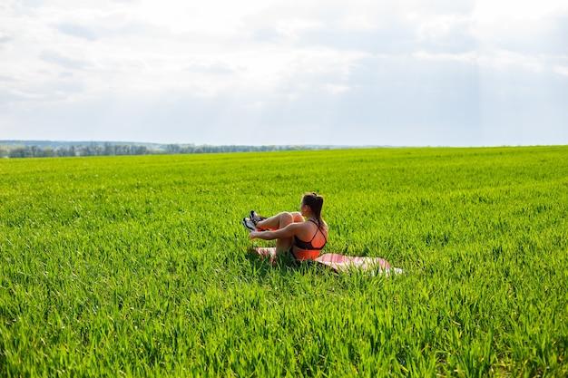 Atleta de menina sacode a imprensa encontra-se em um tapete na natureza. jovem pratica esportes, estilo de vida saudável e corpo atlético.
