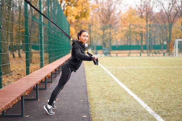 Atleta de menina treinando usando trx no sportground. mulher adulta jovem de raça mista faz exercícios com sistema de suspensão. estilo de vida saudável. alongamento playground ao ar livre.