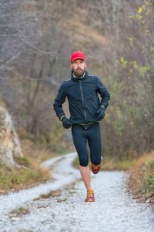 Atleta de montanha de trilha durante o treinamento na estrada de terra
