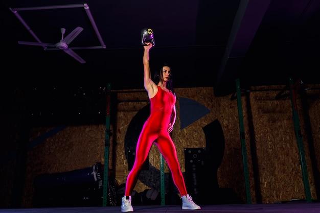 Atleta de mulher atraente ajuste realizando um balanço de sino de chaleira no ginásio