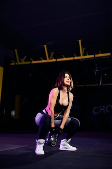 Atleta de mulher atraente de meia idade realizando um balanço de sino de chaleira no ginásio apto a cruz
