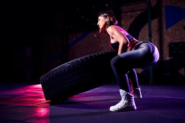 Atleta de mulher atraente meia idade malhando com um pneu enorme, girando e lançando no ginásio. cross fit mulher exercitando com pneu grande