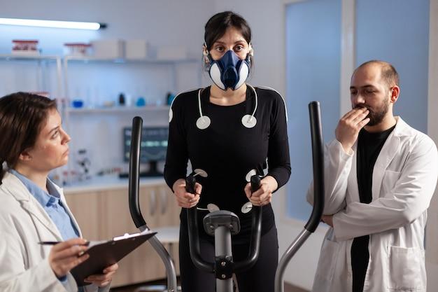 Atleta de mulher com máscara fazendo exercícios de fitness no laboratório de esporte de ciências com eletrodos anexados enquanto cientista segurando a prancheta, supervisionando todo o processo. médico usando o bloco de notas que controla os dados do ekg.