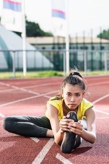 Atleta de mulher, estendendo-se na pista de corrida antes de executar