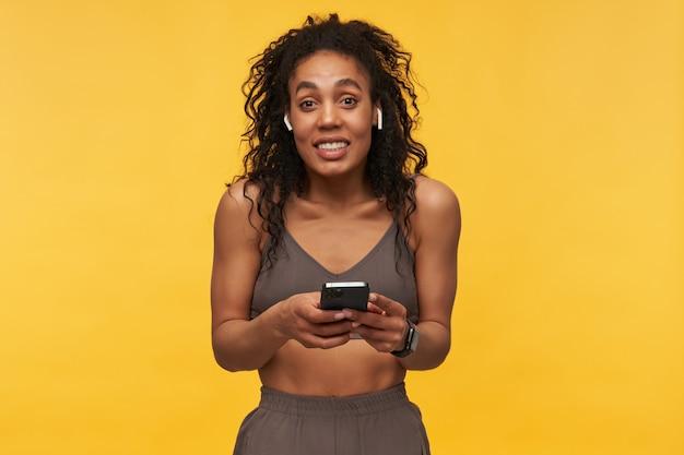 Atleta de mulher jovem e bonita confusa dando de ombros e usando telefone celular e fones de ouvido sem fio isolados sobre a parede amarela