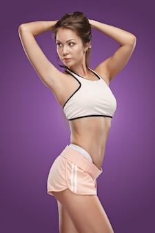 Atleta de mulher jovem e musculosa posando no estúdio em fundo lilás