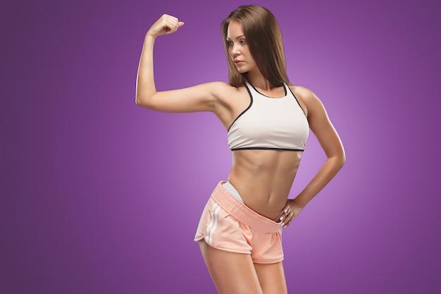 Atleta de mulher jovem e musculosa posando no estúdio em lilás