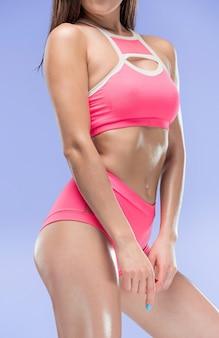 Atleta de mulher jovem e musculosa posando no estúdio sobre fundo azul