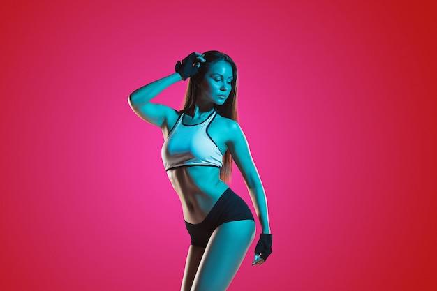 Atleta de mulher jovem e musculosa posando no estúdio sobre fundo vermelho