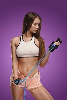 Atleta de mulher jovem e musculosa posando no estúdio
