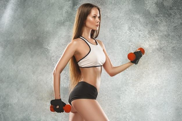 Atleta de mulher jovem e musculosa posando
