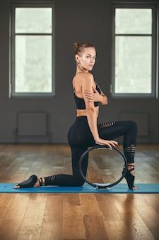 Atleta de mulher jovem modelo fitness em sportswear, fazendo exercícios de alongamento com expansor de borracha. imagem de conceito de estilo de vida saudável de musculação, espaço de cópia.