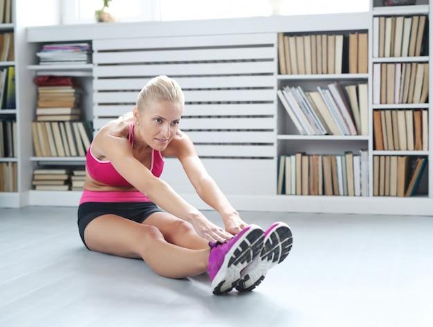 Atleta de mulher loira fazendo alongamento em casa