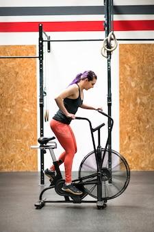 Atleta de mulher malhando em uma bicicleta ergométrica