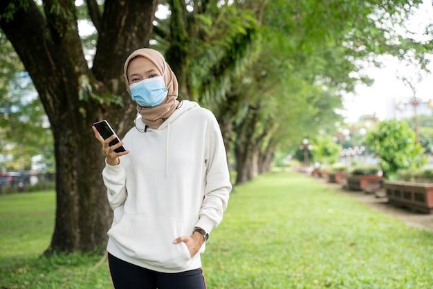 Atleta de mulher muçulmana bonita com máscara facial olhando para a câmera enquanto faz exercícios ao ar livre
