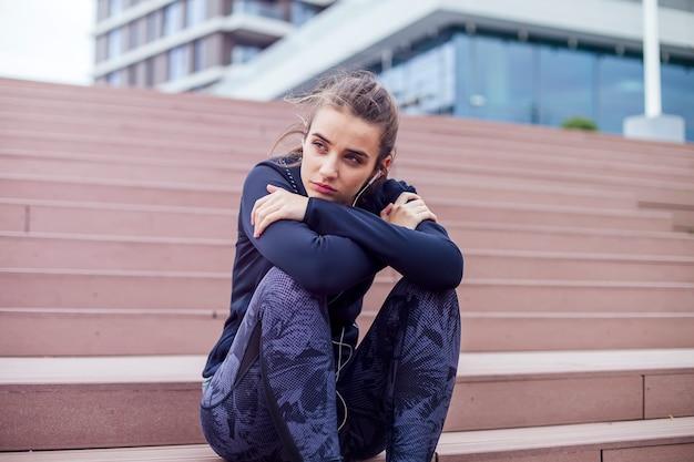 Atleta de mulher sentada na escada enquanto ouve música durante o exercício de jogging