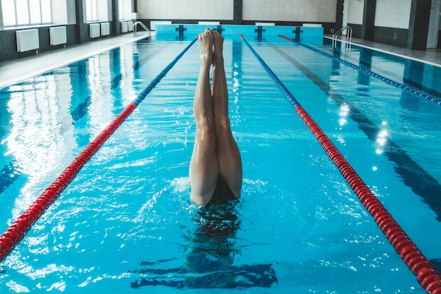 Atleta de natação sincronizada treina sozinho na piscina