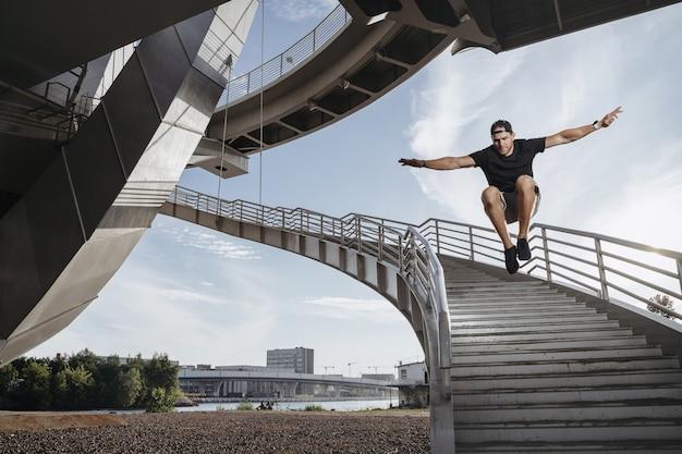 Atleta de parkour dando um belo salto em altura da escada. homem realizando sua habilidade de freerun.