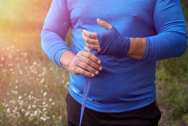 Atleta de pé e enrole as mãos em bandagem elástica têxtil azul
