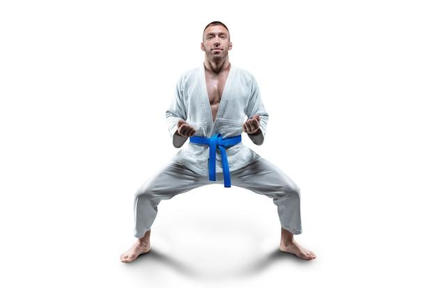 Atleta de quimono com faixa azul fica em posição de combate. conceito de caratê, sambo, jiu-jitsu. mídia mista