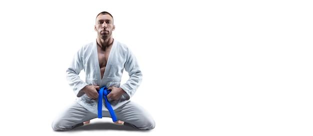 Atleta de quimono com faixa azul senta e espera o adversário. conceito de caratê, sambo, jiu-jitsu. mídia mista