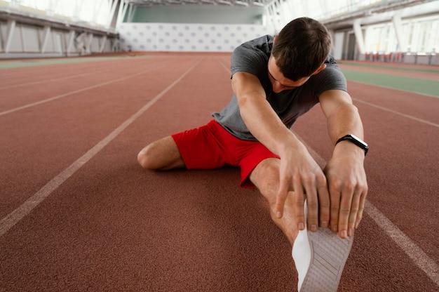 Atleta de tiro completo alongando perna