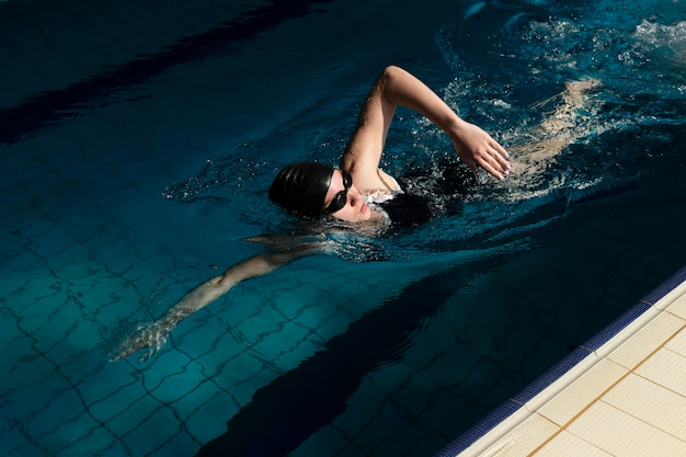 Atleta de tiro completo nadando na piscina