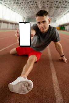 Atleta de tiro completo segurando o telefone