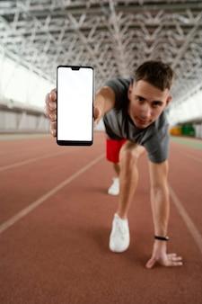 Atleta de tiro completo segurando smartphone