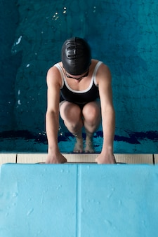 Atleta de tiro completo usando touca de natação