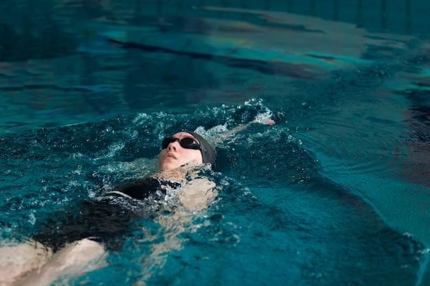 Atleta de tiro médio nadando com óculos de proteção
