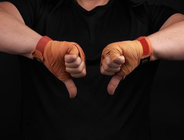 Atleta de uniforme preto e mãos rebobinadas com bandagem laranja têxtil mostra gesto de antipatia