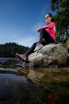 Atleta descansando a la orilla de uma lagoa sentada sobre uma piedra após correr no bosque