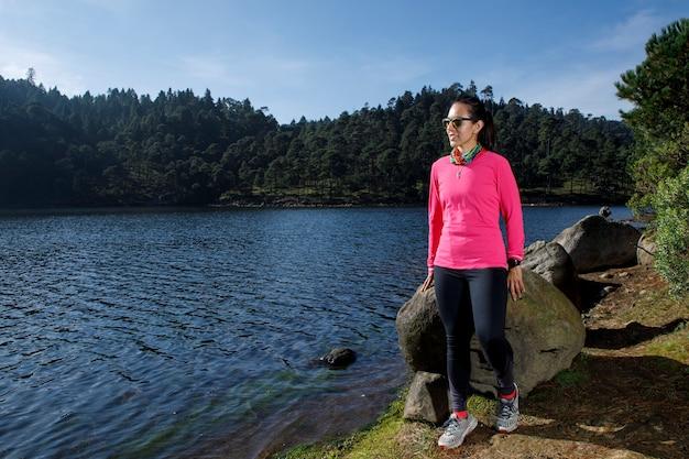 Atleta descansando na orilla de um lago depois de correr no bosque rodeado de arboles