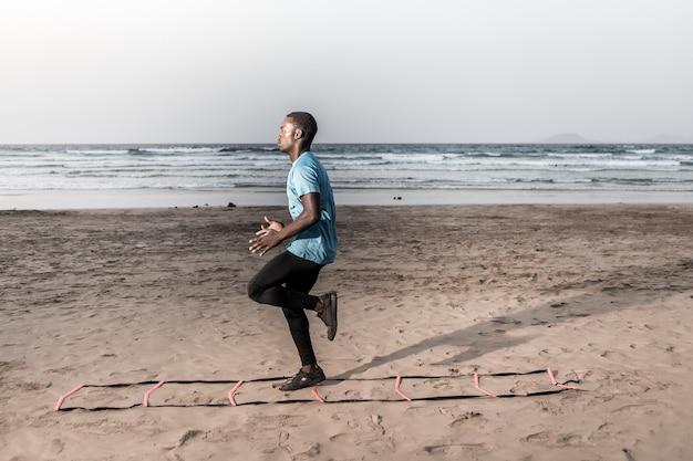 Atleta determinado fazendo exercício em escada na praia